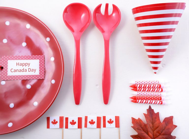 Canada Party Table Background with red and white plates, Canadian flags, and maple leaf decorations.