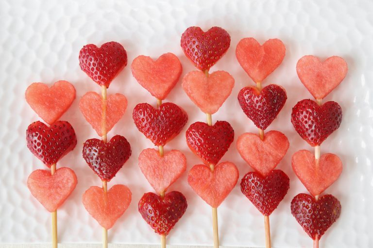 heart shape strawberry and watermelon fruit skewers on white plate, fun food art