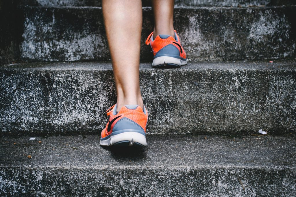An image of a person running up the stairs. Only showing ankles and feet.