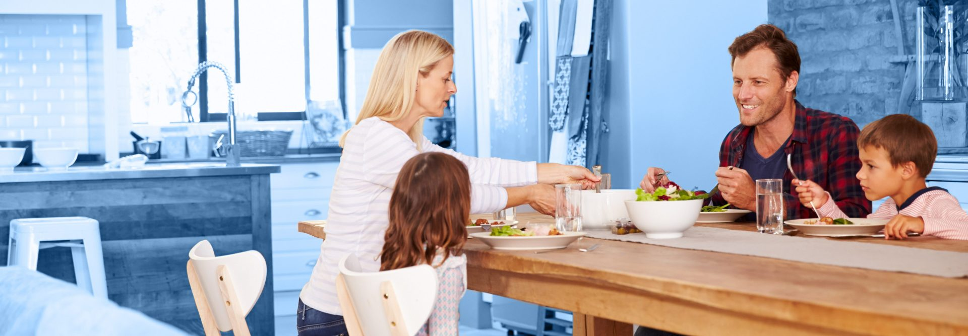 Parents and 2 children eating a meal at their kitchen table
