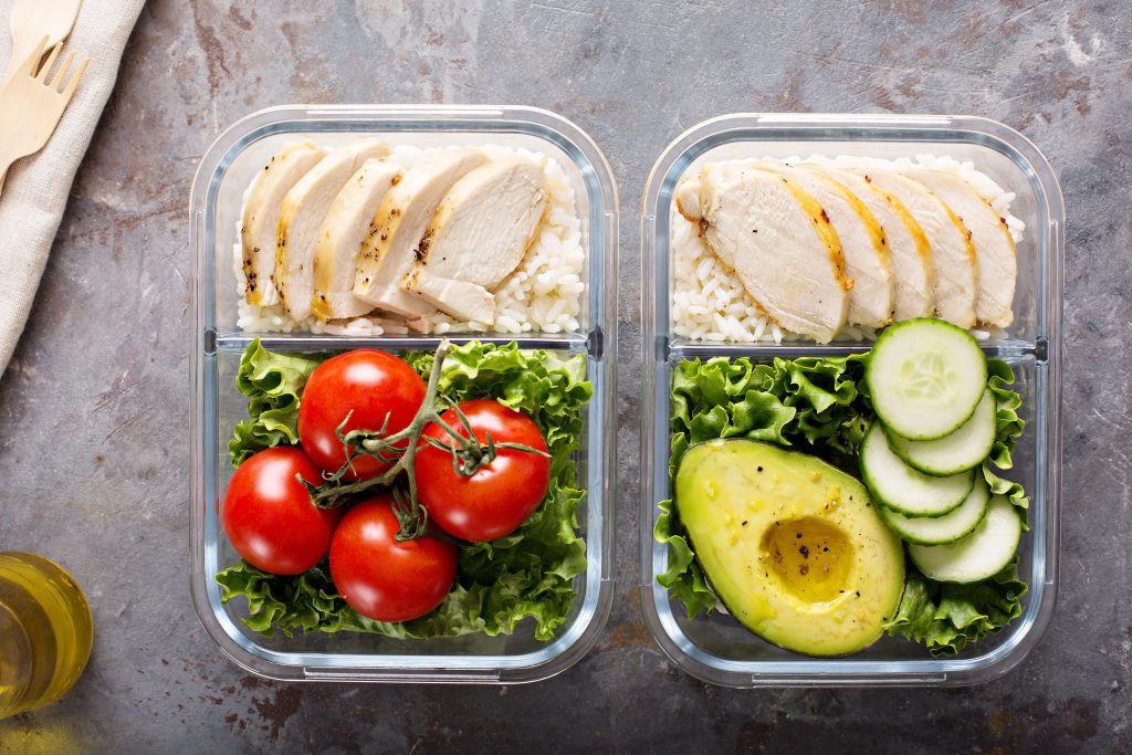 2 glass containers with prepared meals in them