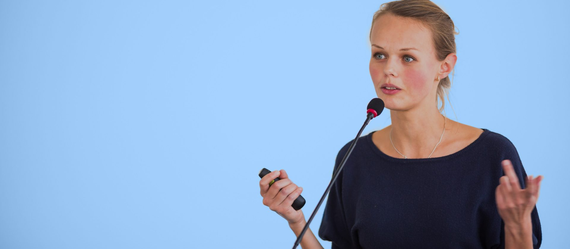 A female speaker standing alone facing the audience