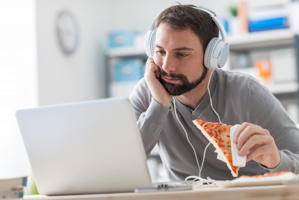 A man eating pizza by a laptop