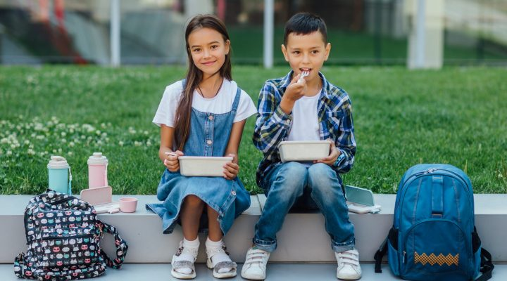 two school children eating a lunch outside