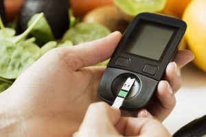 Diabetes monitor in a persons hand, healthy foods