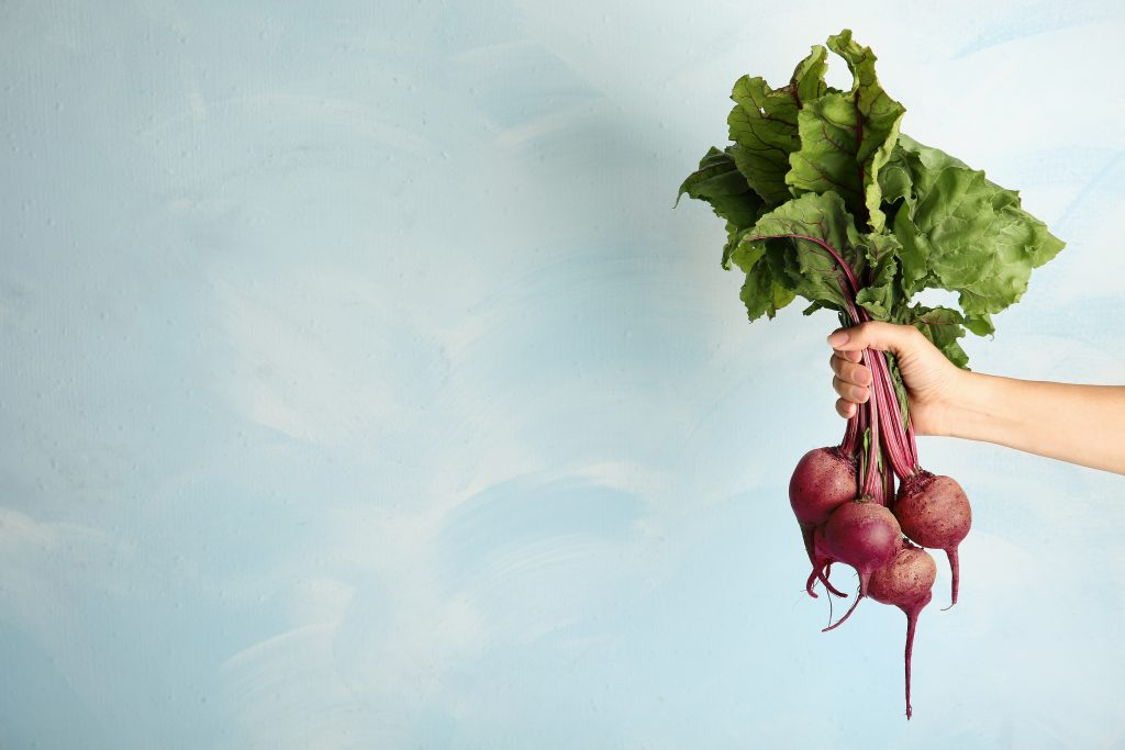 A hand holding a bunch of beets