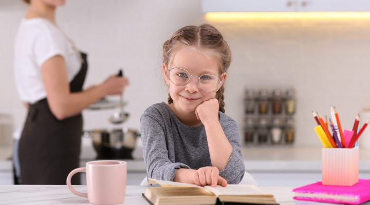 Nutrition Learning Ideas for parents. A girl doing home work at kitchen island while mother is cooking.