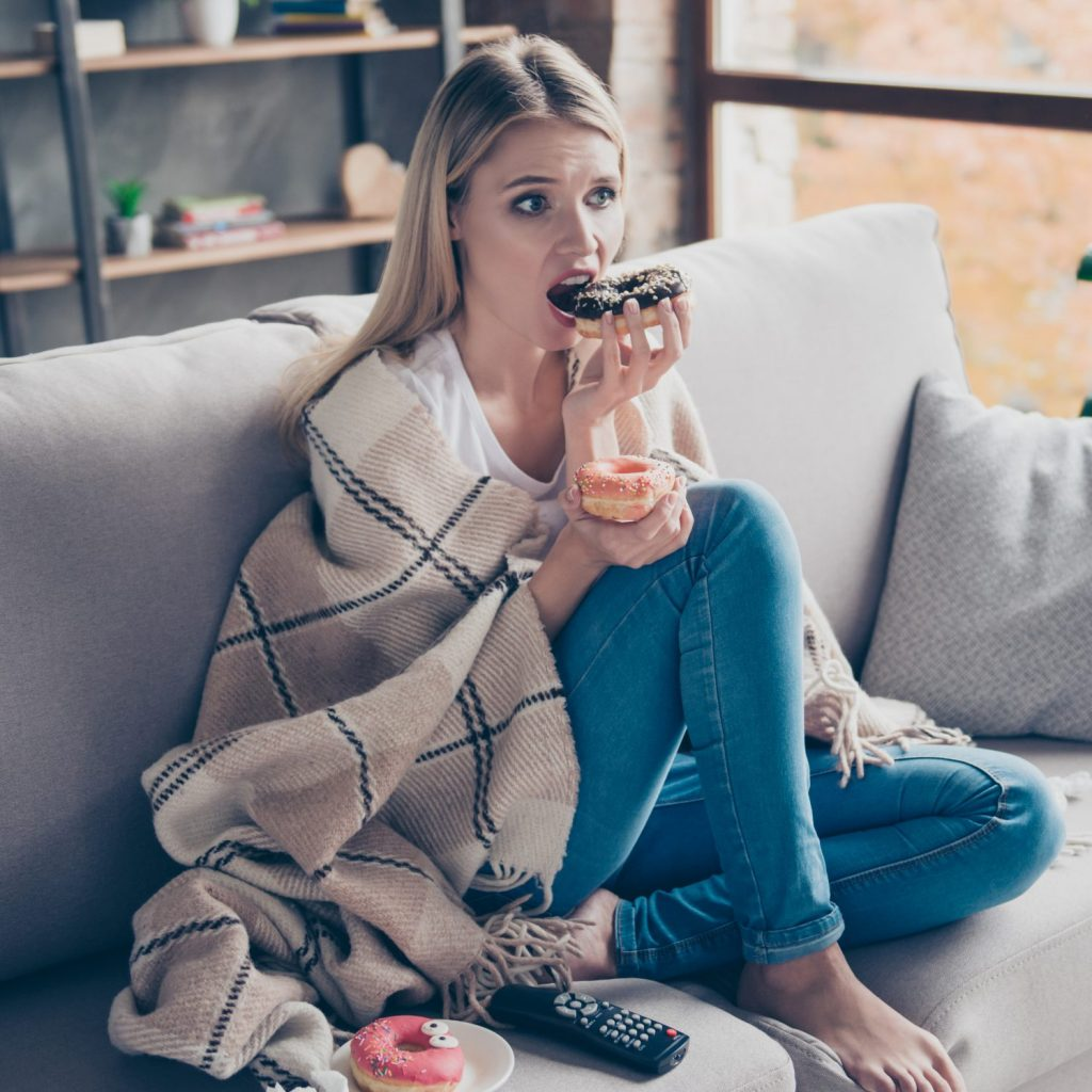 An upset woman eating donuts on the sofa
