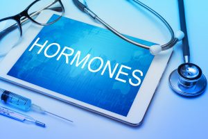 tablet with the word hormones on the screen, stethoscope