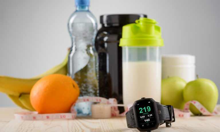 A set for a sportsman to be in shape. Sports watch for being organized, fruits as oranges, apples and bananas, shaker with protein cocktail, cans with sport supplements and mineral water on the desk.
