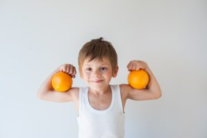 A boy holding oranges on his biceps and posing