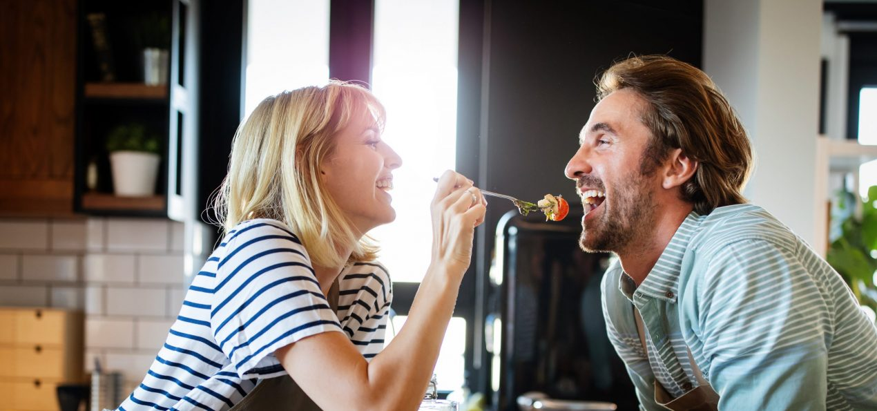 Happy couple cooking together. Husband and wife in their kitchen at home preparing healthy food in their kitchen