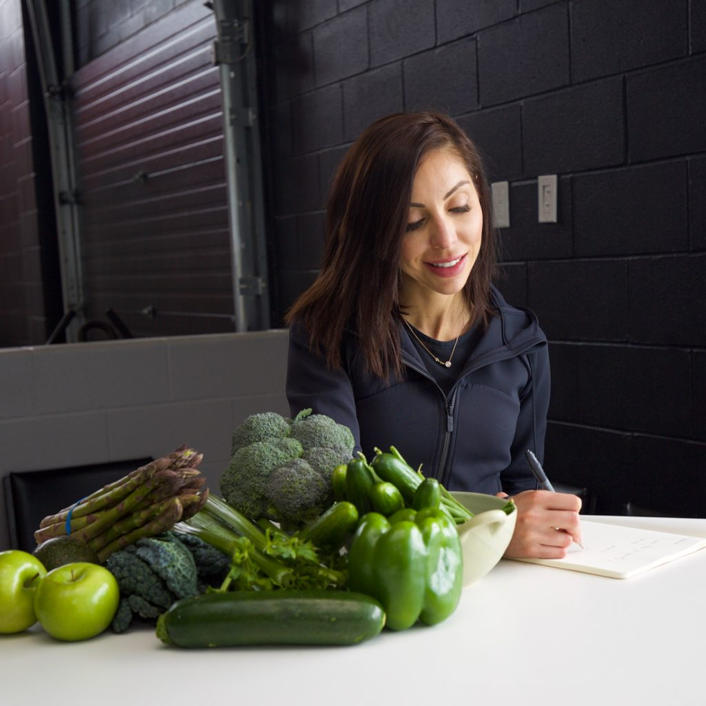 An image of Lisa spriet planning sport nutrition for a client. Picture includes green vegetables on the table