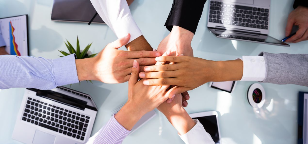 Group Of Businesspeople Stacking Hands Over Desk In Office