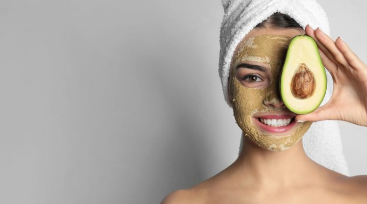 Young woman with clay mask on her face holding avocado.