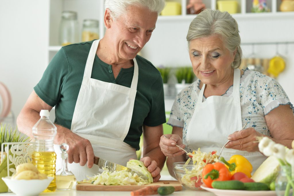 A senior couple cooking together preparing a healthy meal
