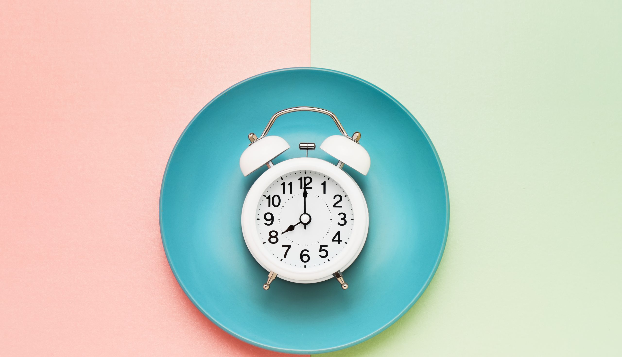 Intermittent fasting concept. White alarm clock on empty blue plate. Top view, copy space