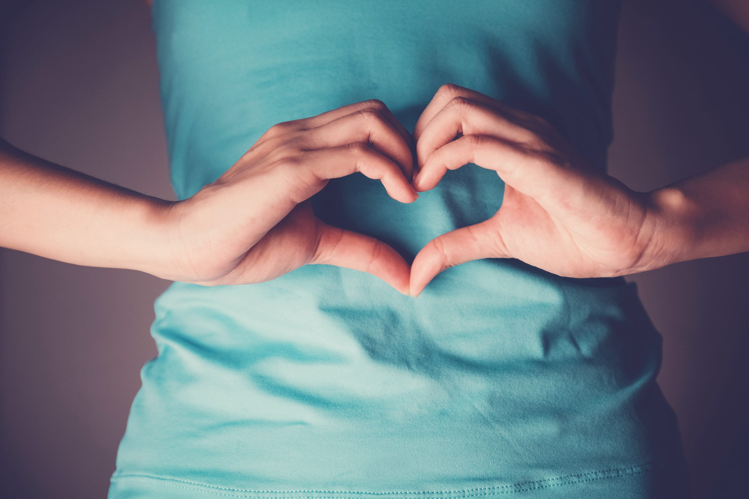 Woman hands making a heart shape on her stomach, IBS, healthy bowel digestion, probiotics for gut health, Sign Language