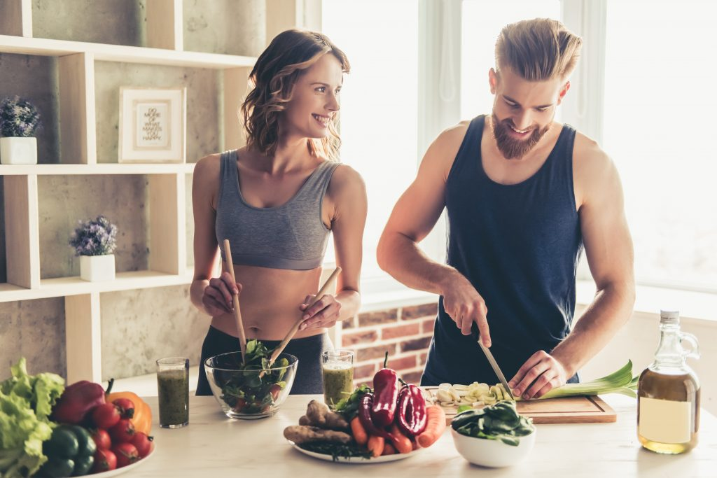 A fit couple following a couples nutrition program and making a meal together.