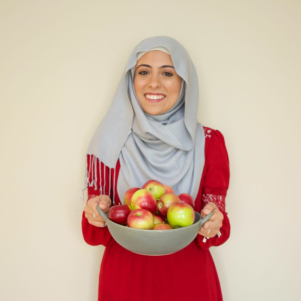 Bissan Ghaith, RD holding a bowl of apples