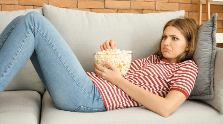 Upset young woman eating popcorn while watching TV at home
