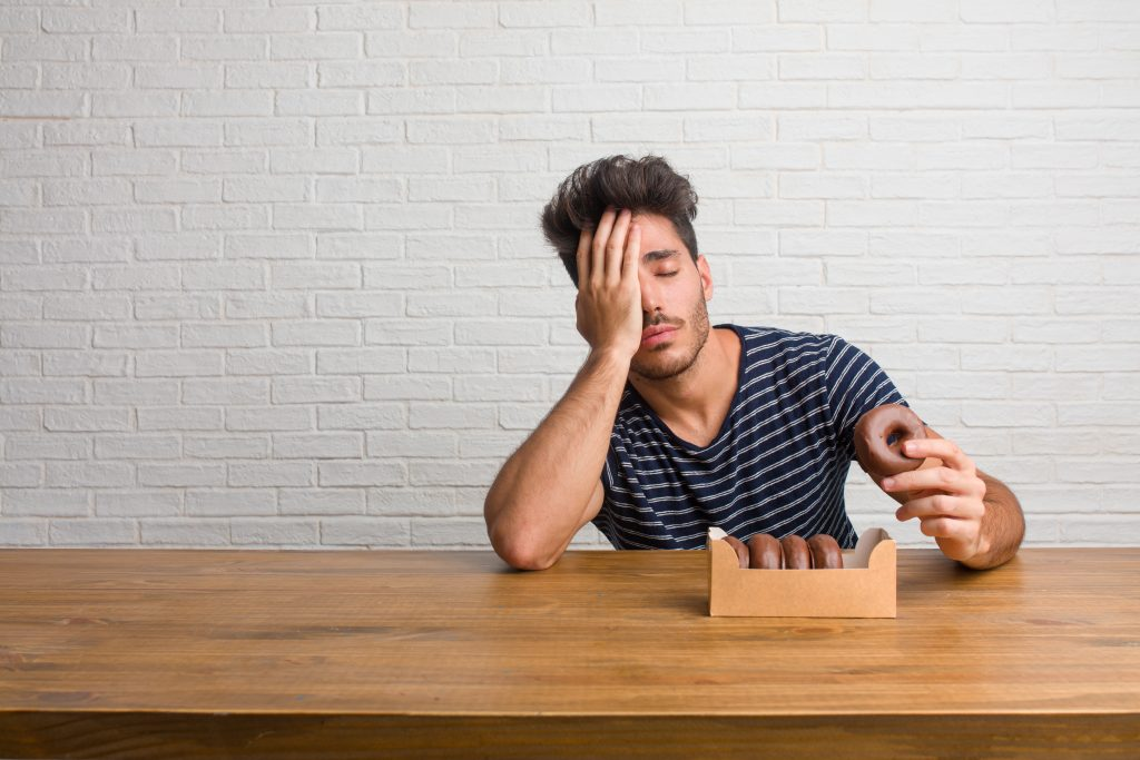 A man looking stressed and tired eating a box of chocolate donuts