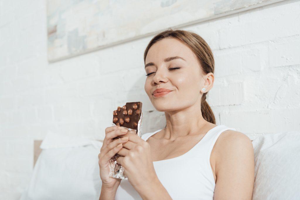 A woman enjoying a large chocolate bar