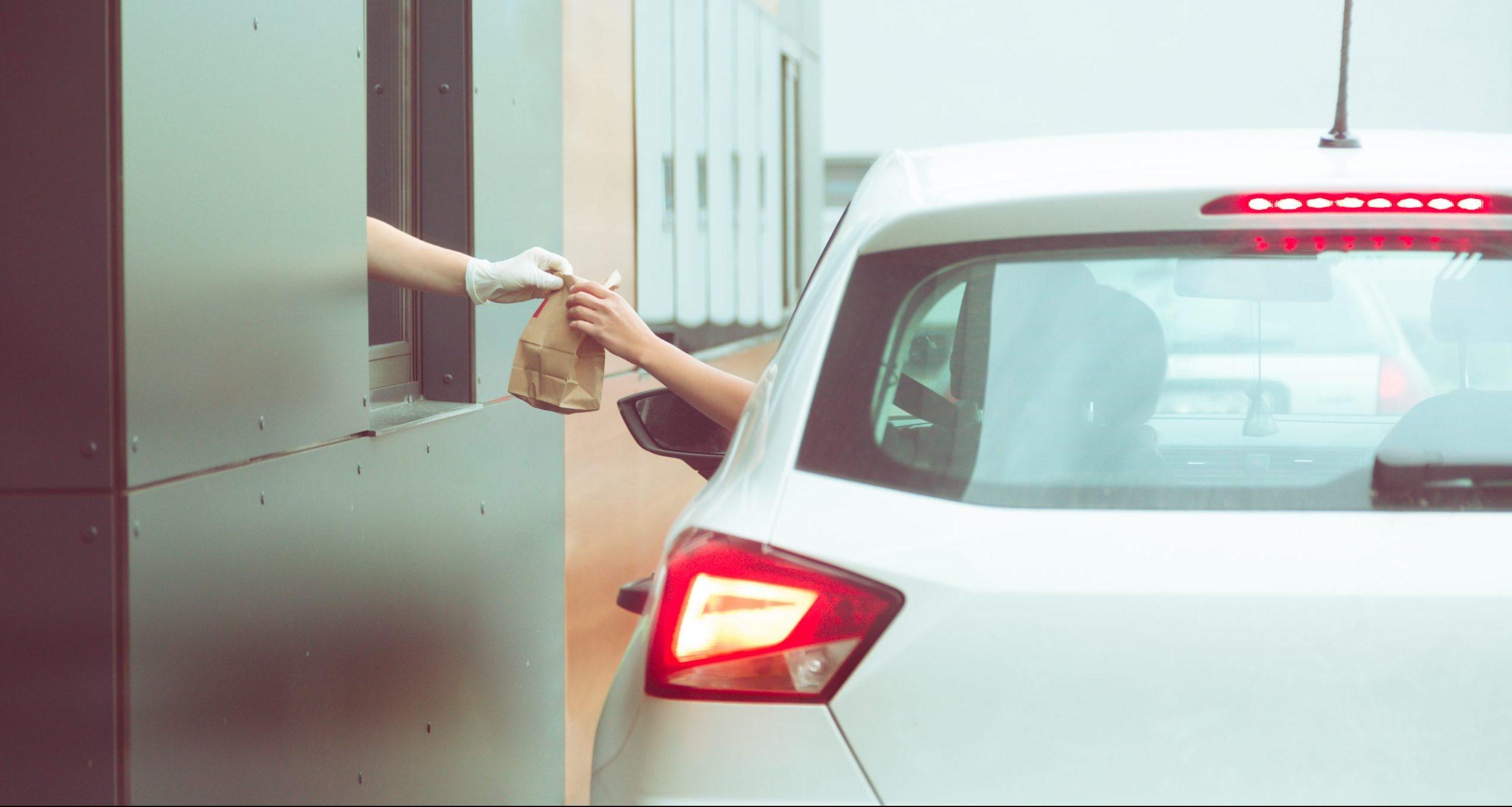 A person receiving a bag of food through a drive-through window