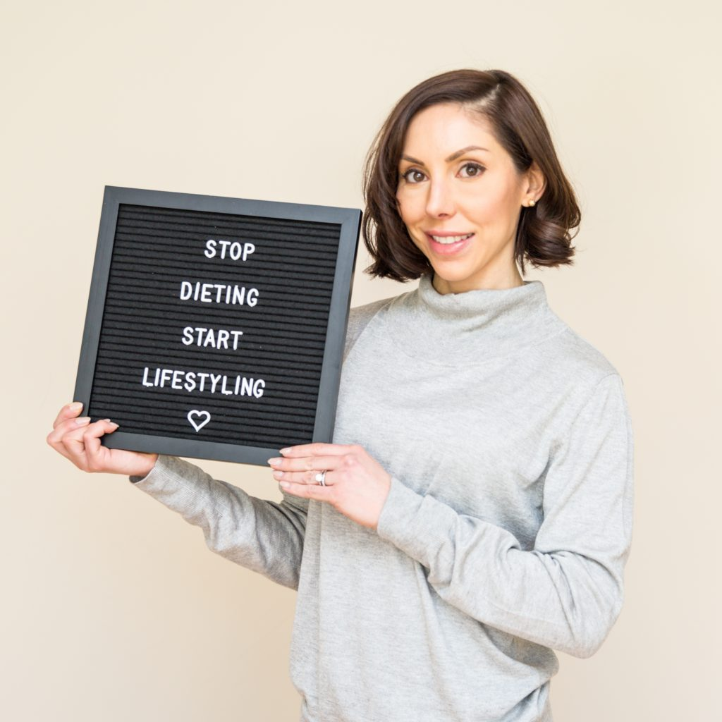 """Lisa Spriet Holding a Sign for """"Stop Dieting, Start Lifestyling"""""""