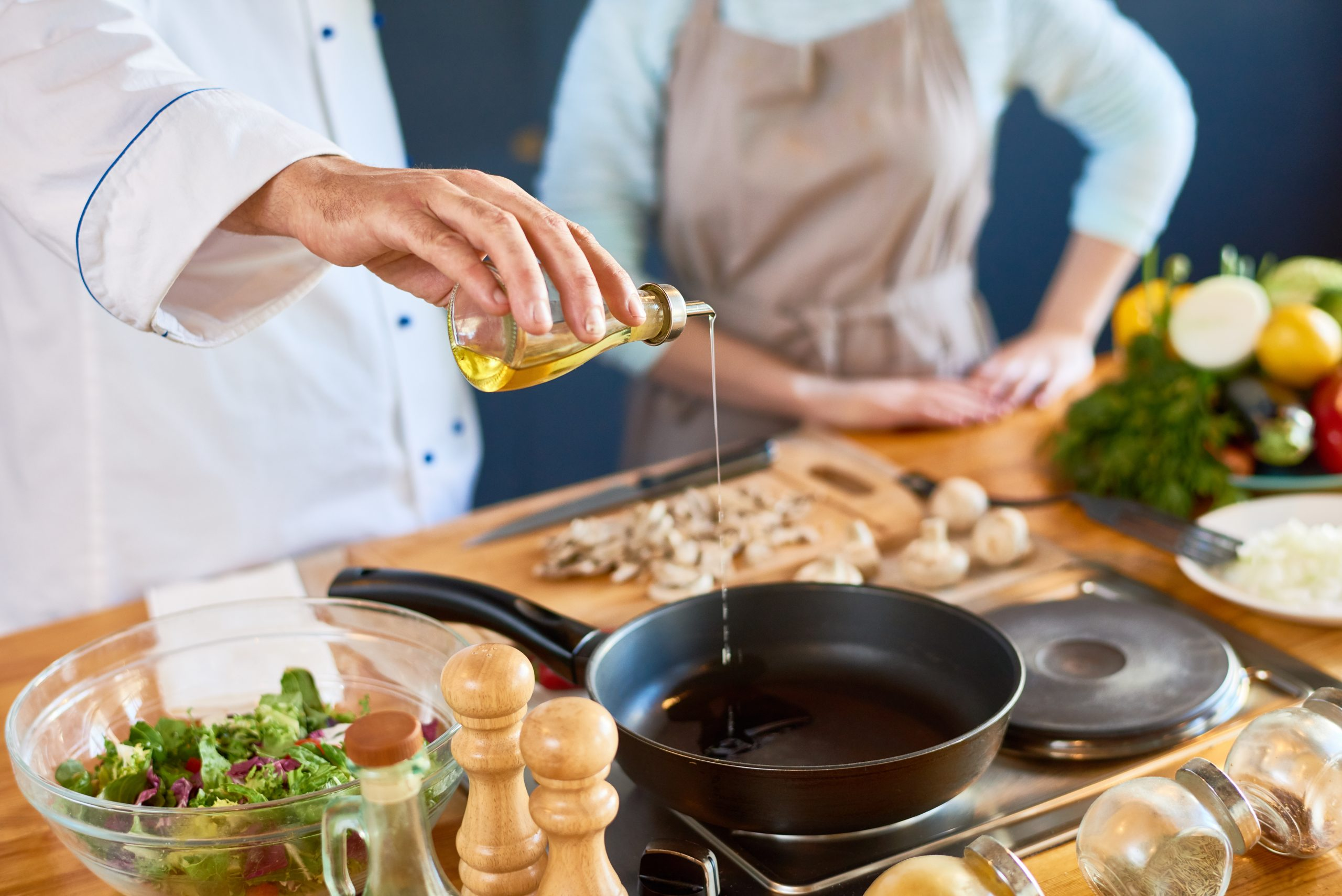 Chef pouring cooking oil on a pan